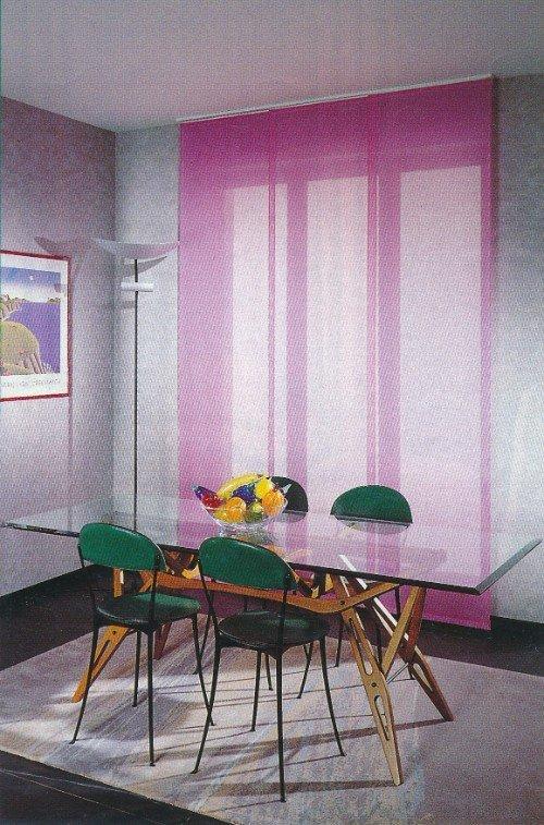 Sala da pranzo con tavola di vetro ,sedie verde e avvolgibile rosa