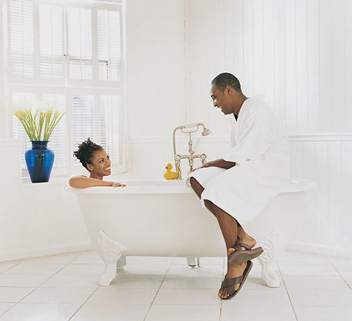 couple sitting and smiling in a beautiful white bathroom