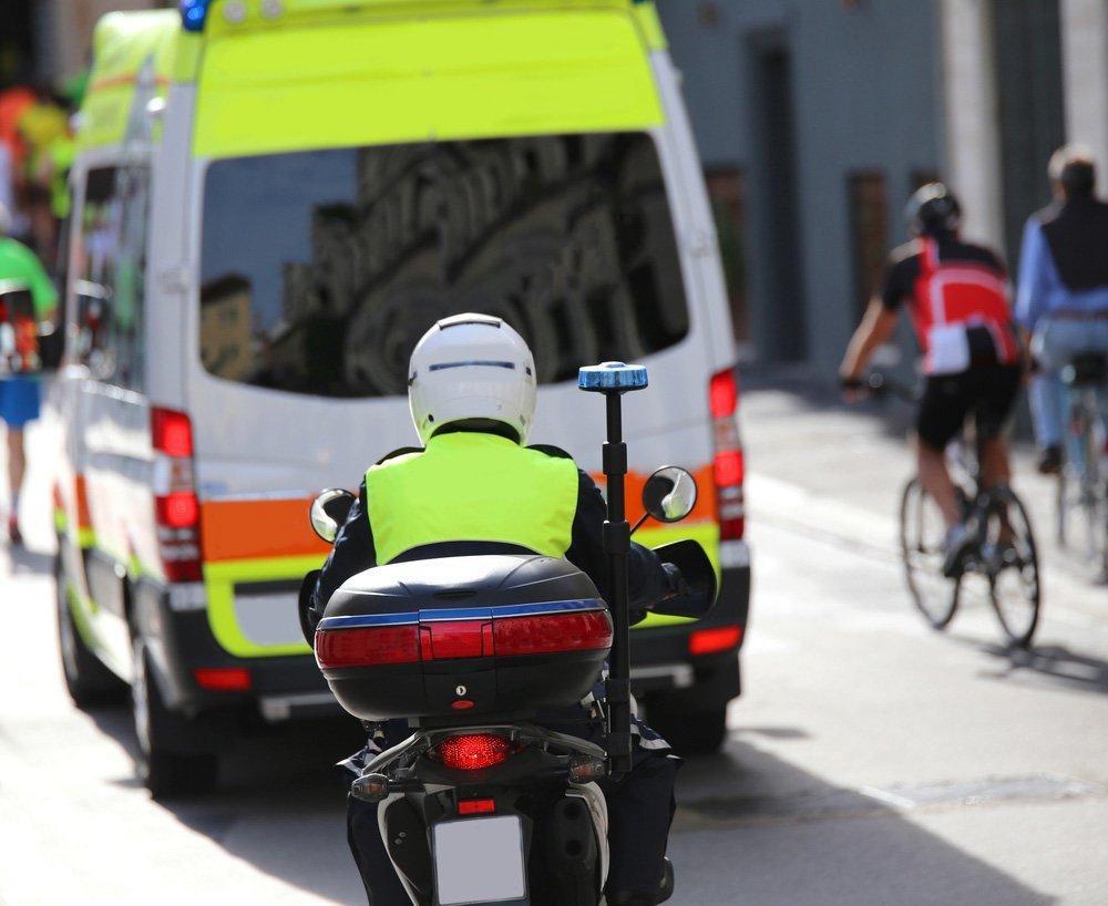uomo in moto che segue un'ambulanza