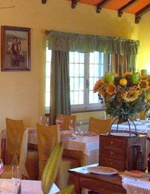 Sala di ristorante arredata con fiori e pareti gialle