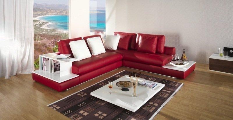 salotto con divano rosso a L con cuscini bianchi