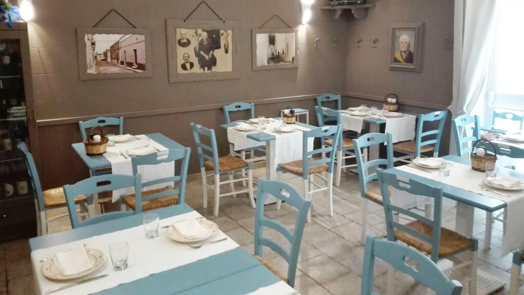 vista dei tavoli con delle sedie azzurre all'interno del locale