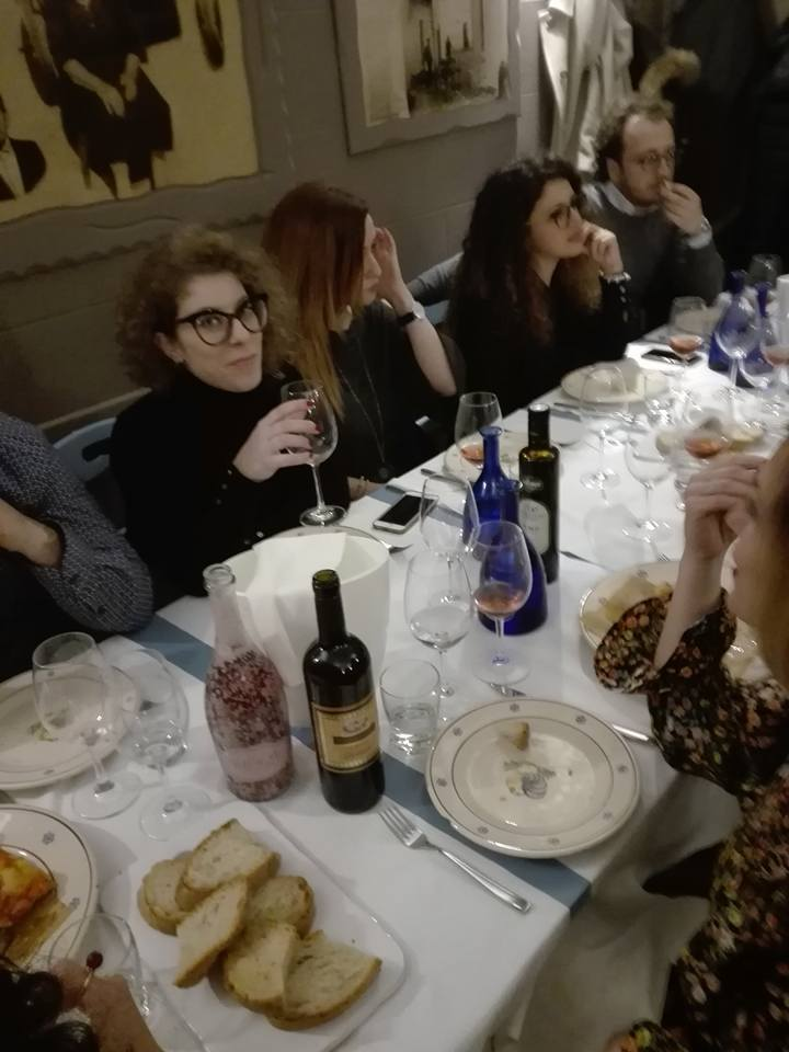 delle persone a tavola mentre mangiano e bevono