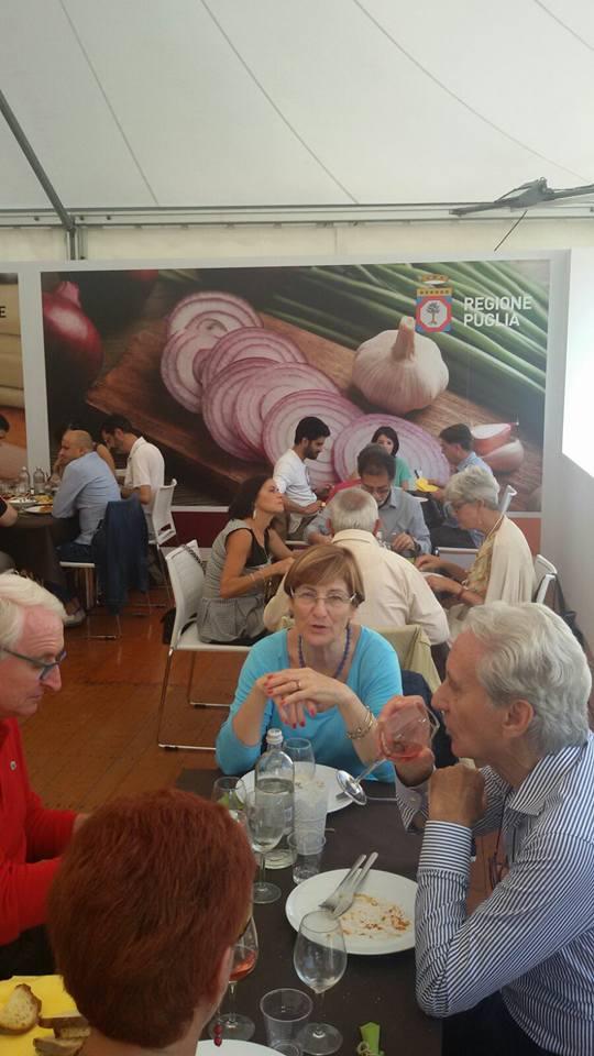 delle persone sedute ai tavoli mentre mangiano