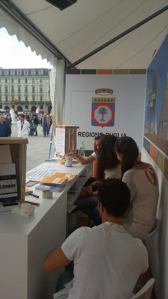 delle persone sedute dietro a un bancone di un stand della Regione Puglia