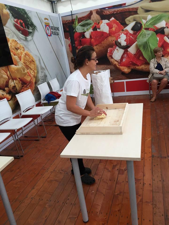 una ragazza in piedi vicino a un tavolo durante un evento della Regione Puglia