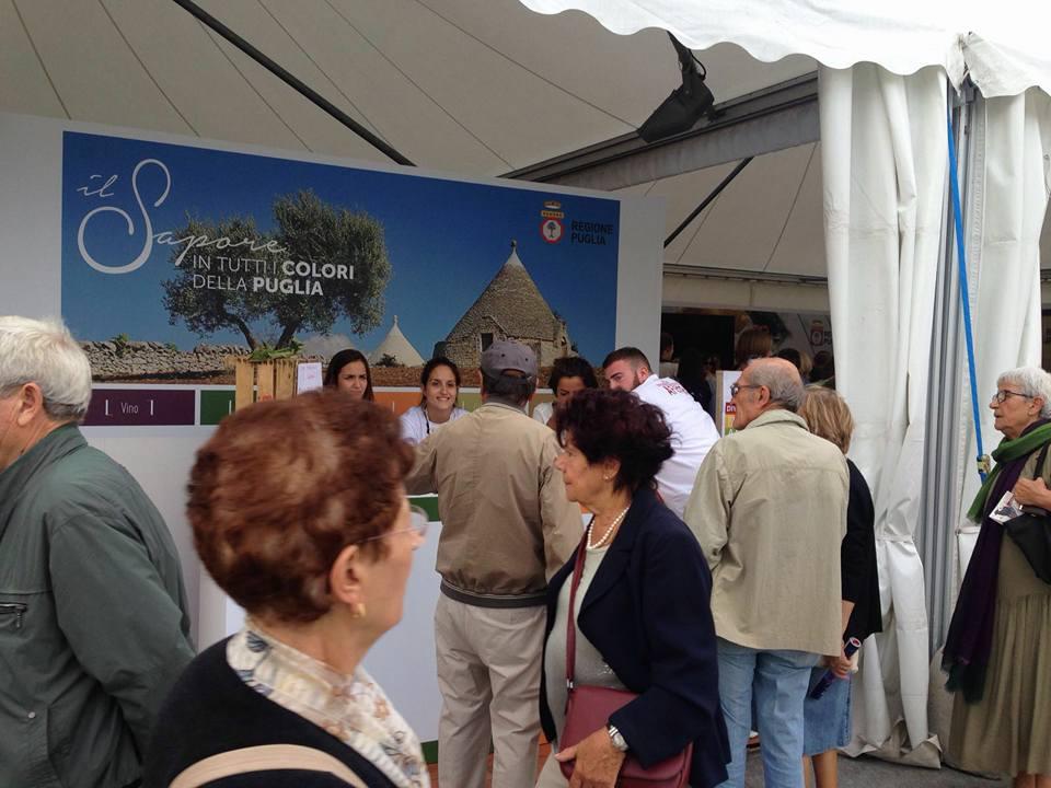 delle persone in piedi e vista di un cartellone con scritto il Sapore in tutti i colori della Puglia