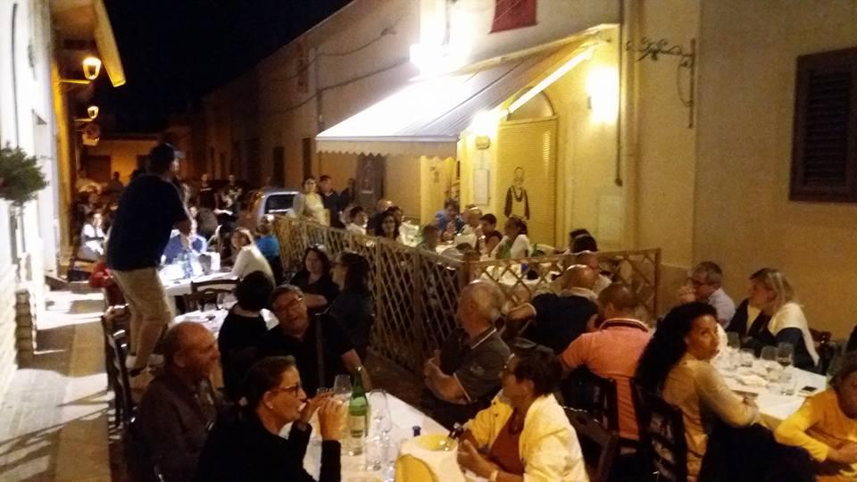 delle persone sedute ai tavoli all'esterno e uno in piedi su una sedia