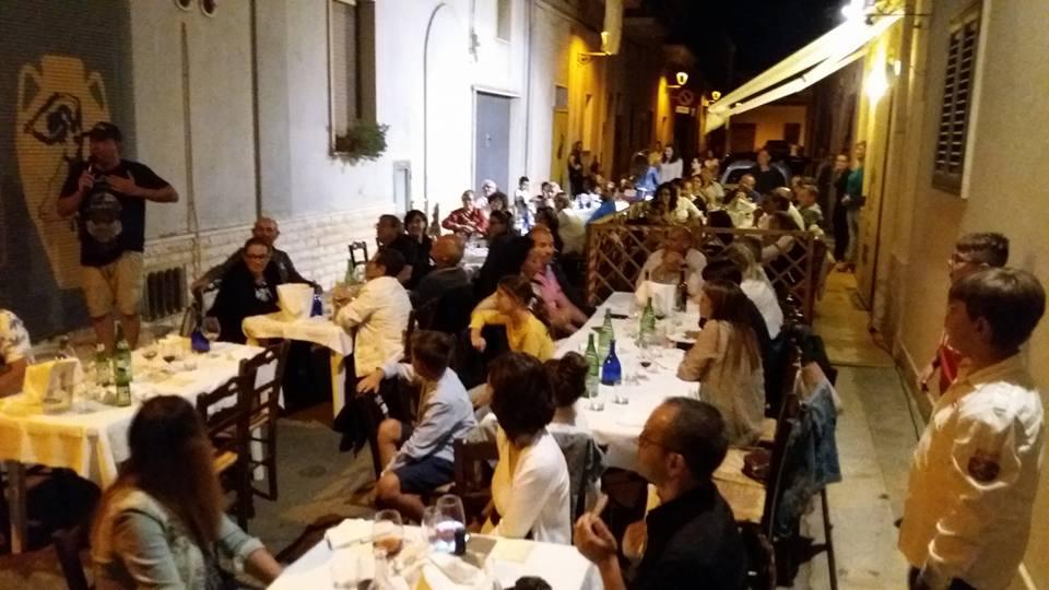 delle persone sedute ai tavoli all'esterno e uno in piedi su una sedia che canta