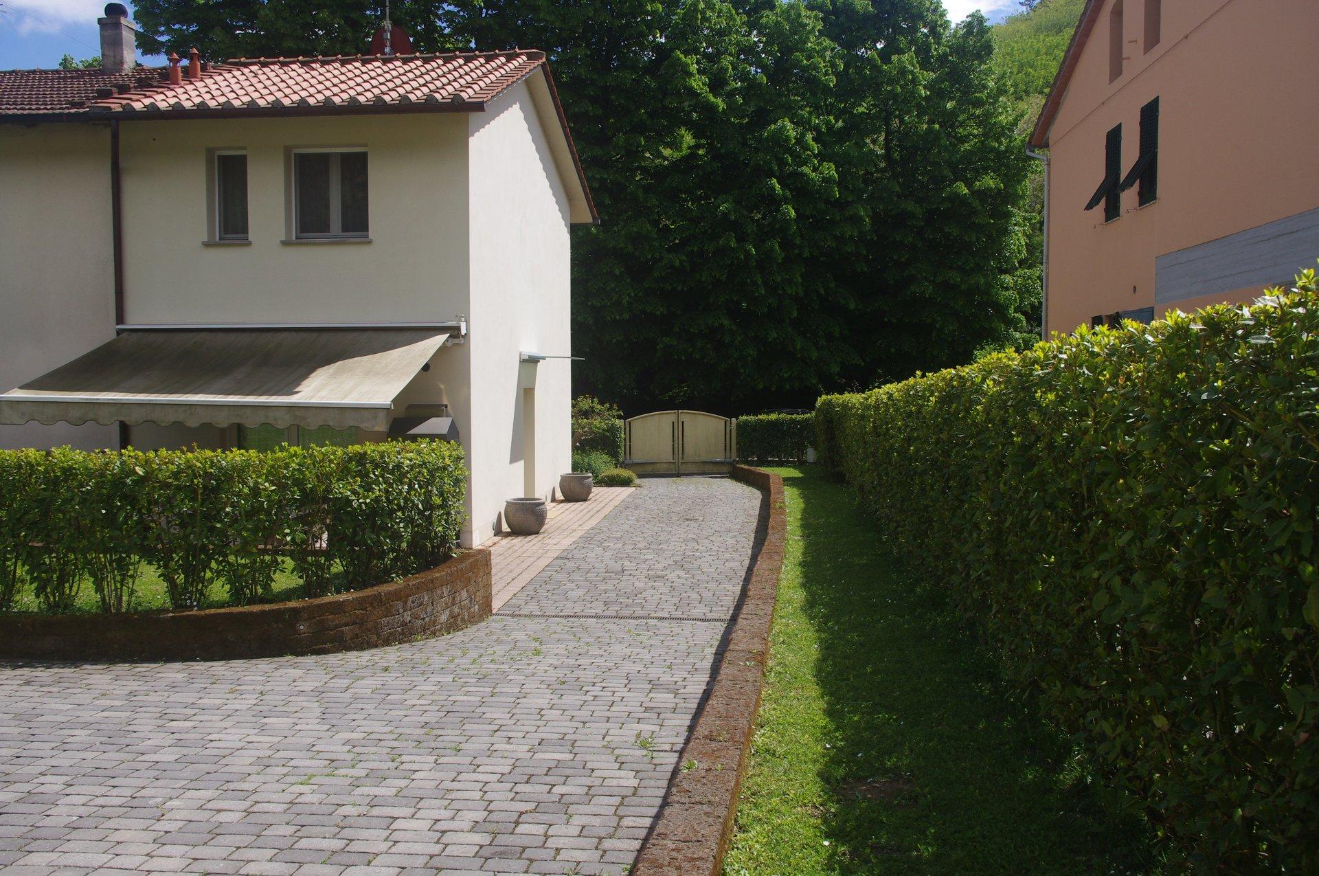 una villa con un pavimento in asfalto intorno e della siepe