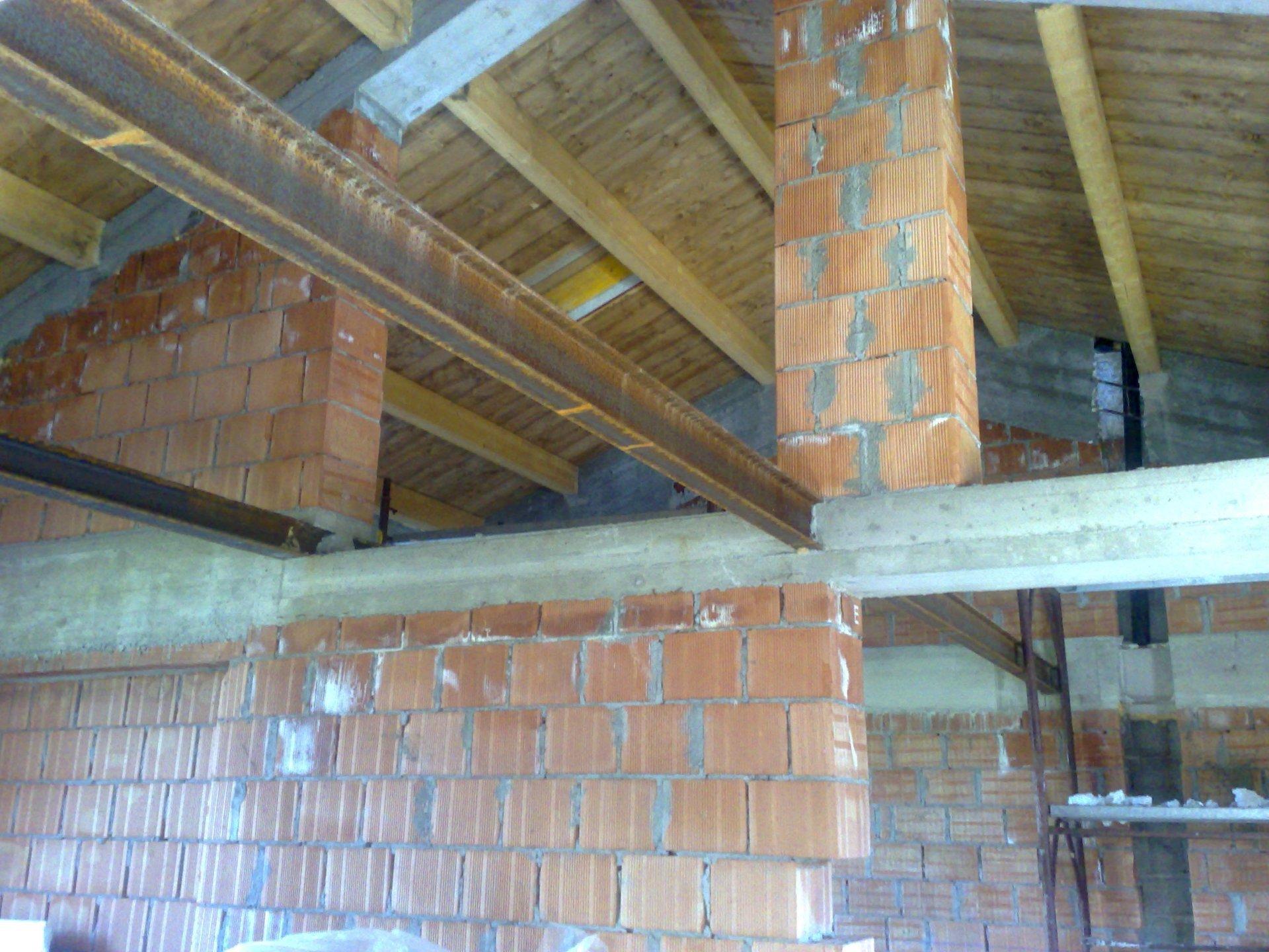 un muro con i mattoni a vista e un tetto in legno