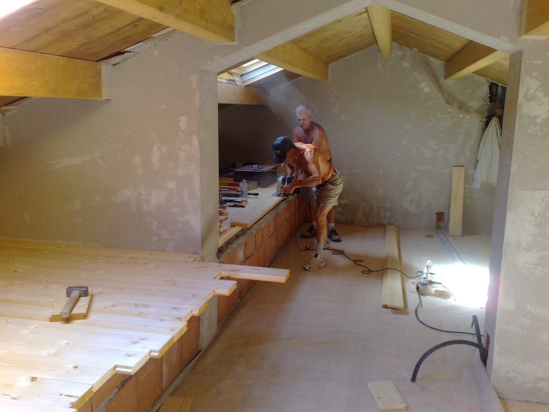 due operai mentre tagliano del legno all'interno di una villa in costruzione