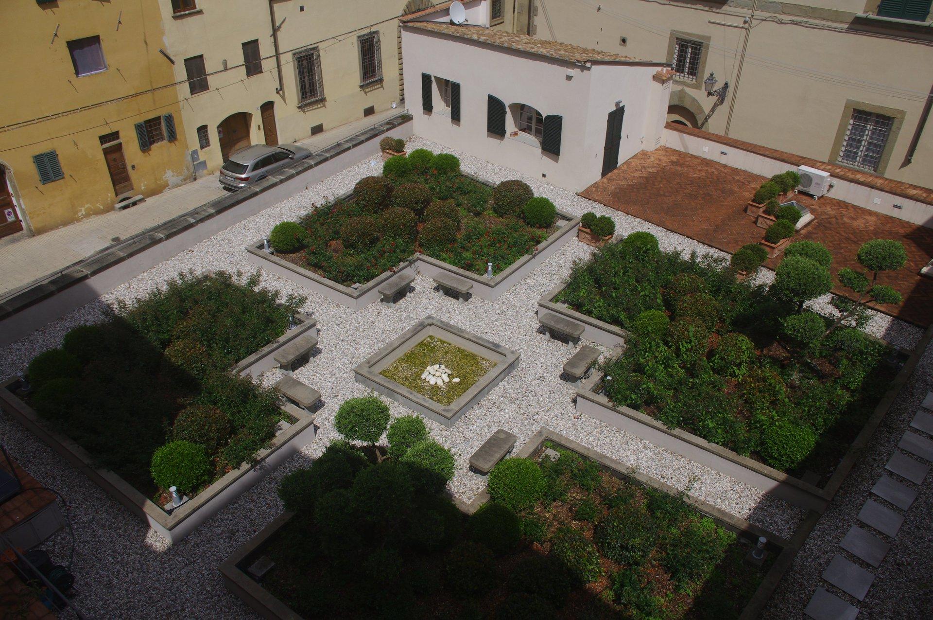 una piazza con quattro aiuole di piante e in mezzo delle panchine