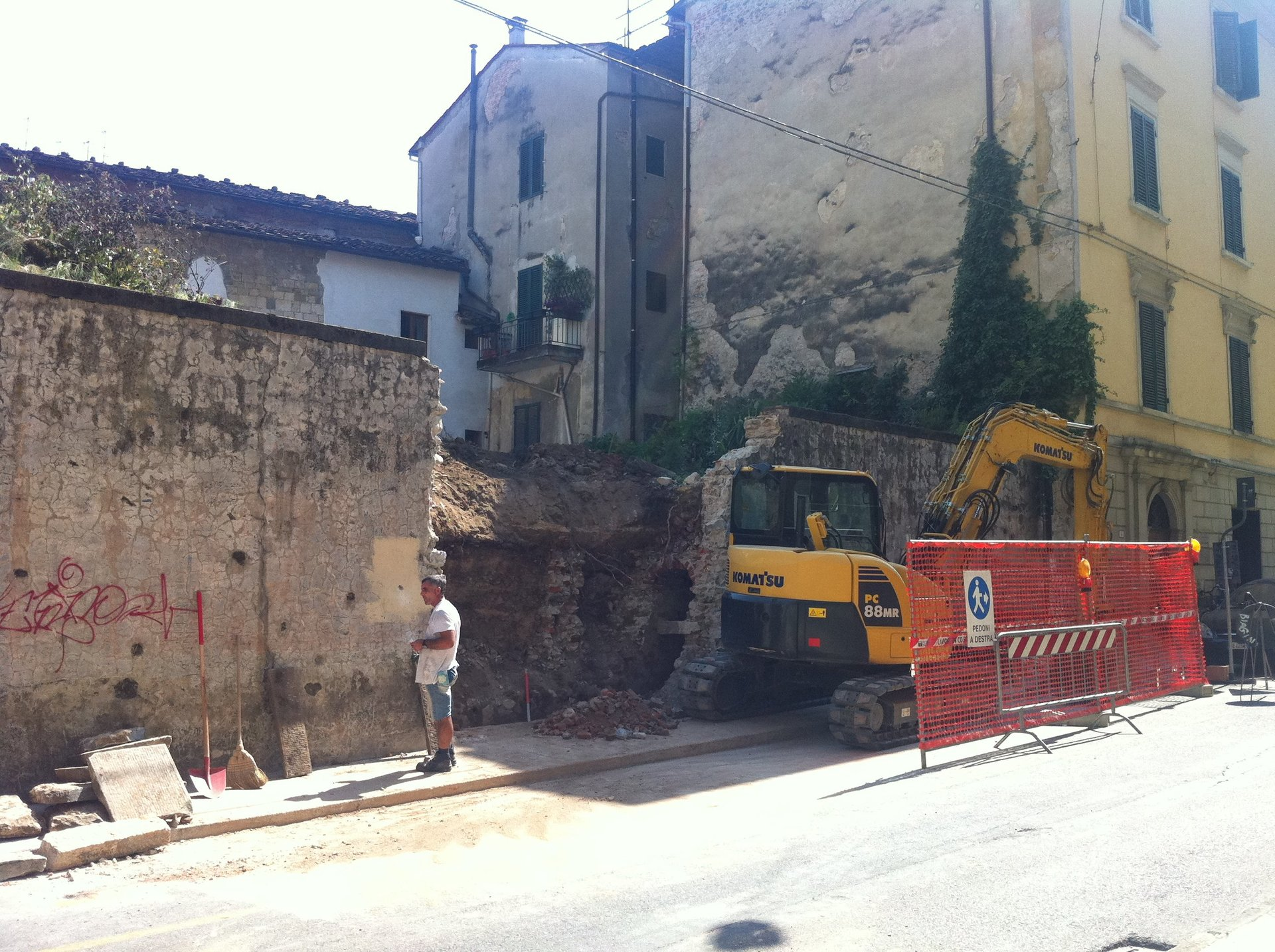una casa demolita e accanto una demolitrice