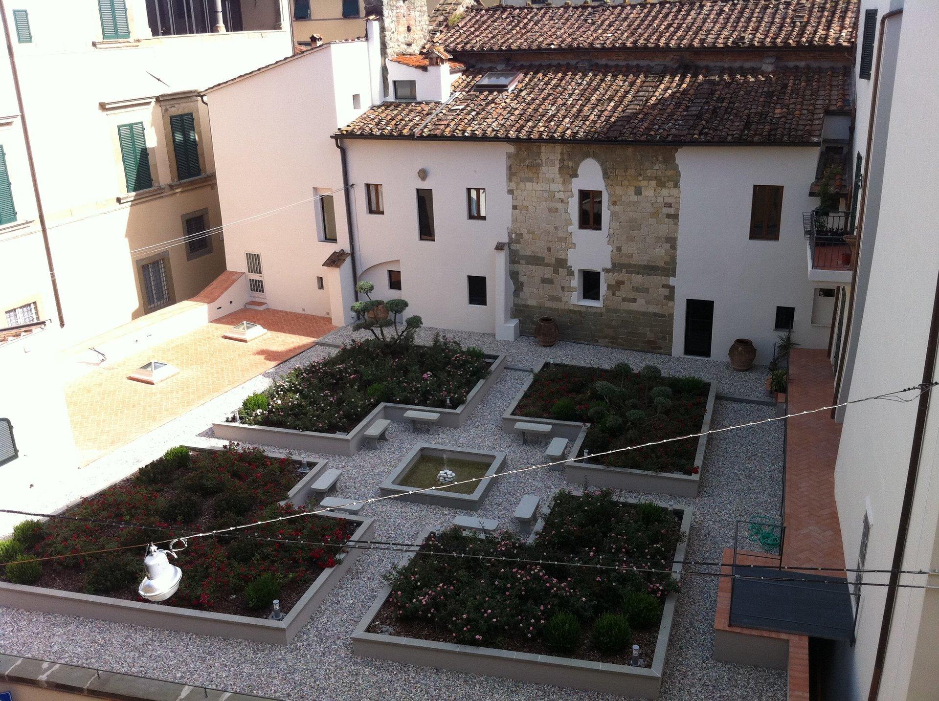 vista delle ville e una piazza con delle aiuole con delle piante e delle panchine