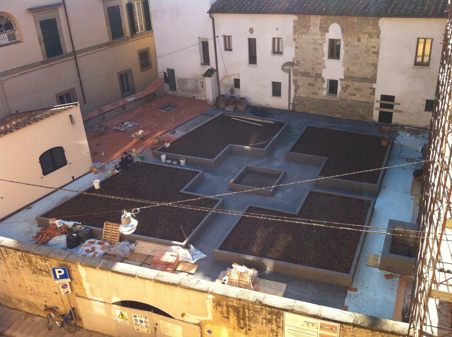 Vista dall'alto delle fondamenta di uno stabile in costruzione e attorno delle case
