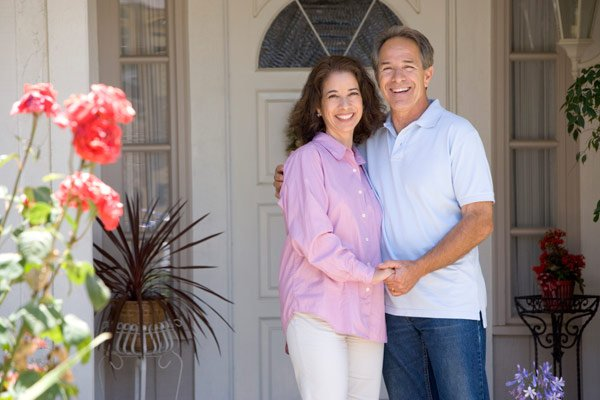 View of smiling couple in front of the house entrance
