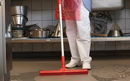 Donna che pulisce il pavimento di una cucina