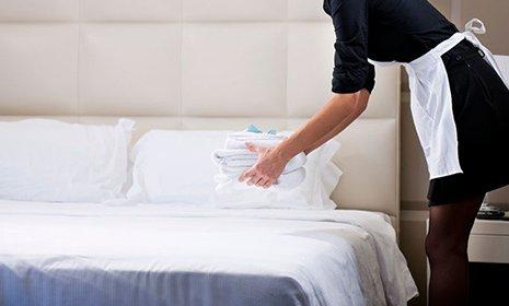 cameriera che appoggia sul letto le lenzuola pulite