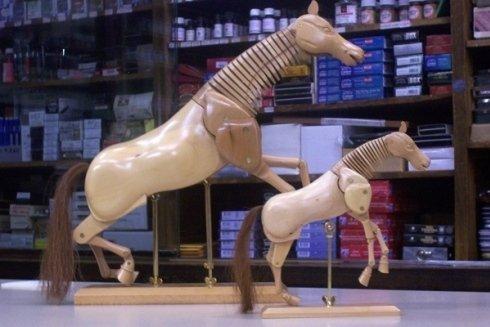 Modellini in legno di cavalli in due diverse scale di grandezza.