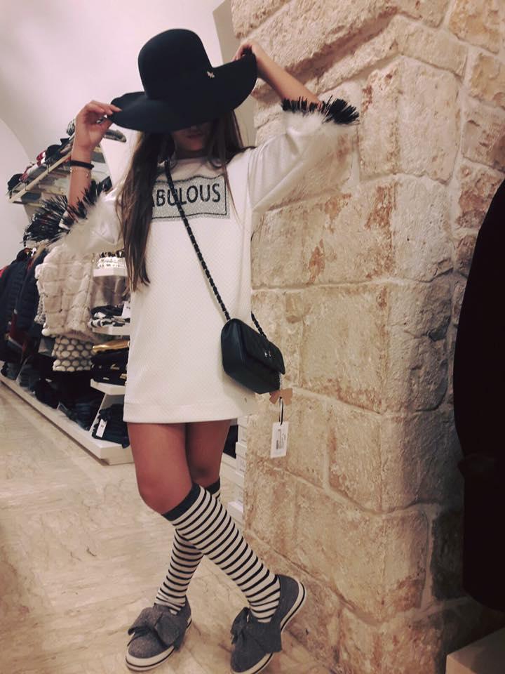 una bambina con una maglietta lunga di color bianco e un cappello nero