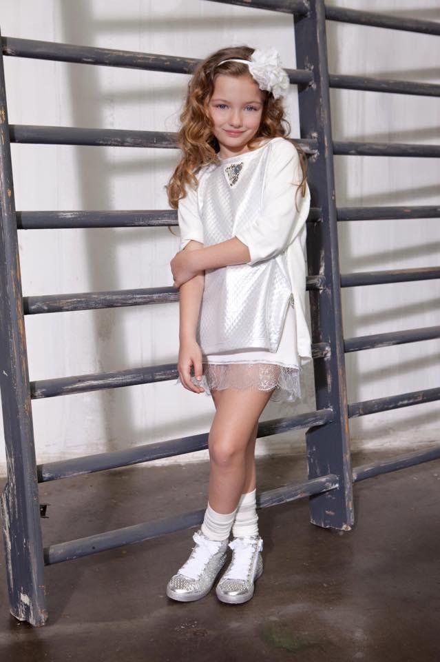 una bambina con una maglietta e delle scarpe di color argento