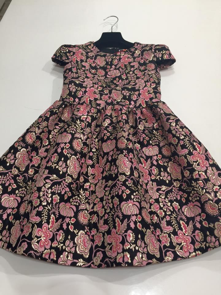 un abito da bambina di color nero con disegni a fiori di color rosa e oro