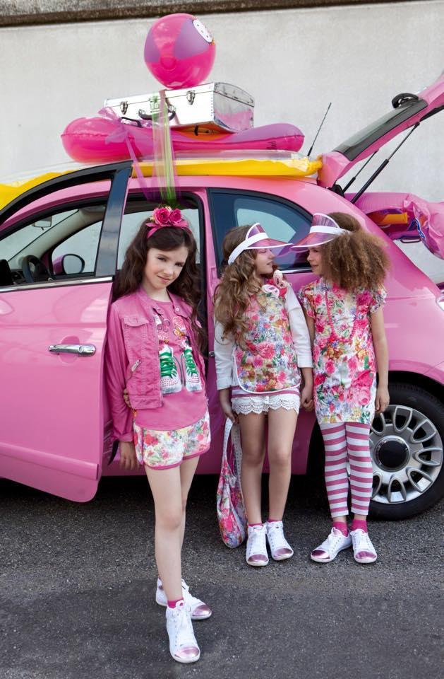 tre ragazzine vestite in rosa e disegni a fiori accanto una macchina rosa