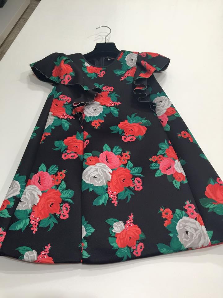 un abitino da bambina di color nero con disegni a fiori rosso, bianco e verde