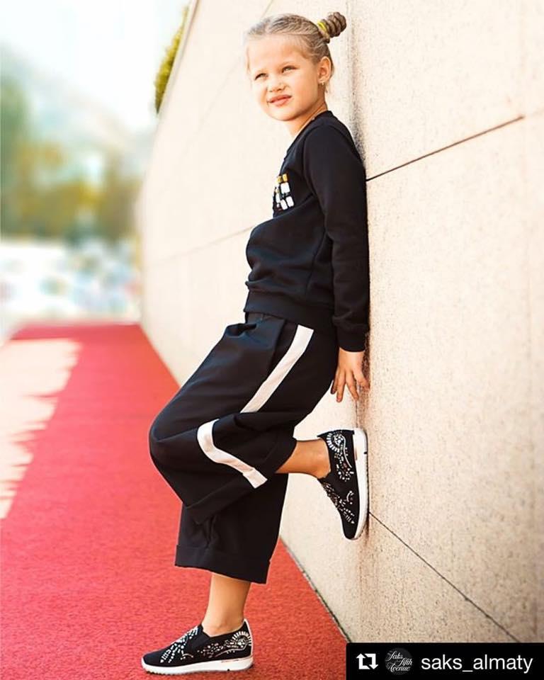 una bambina con dei pantaloni neri e una maglia di color nero