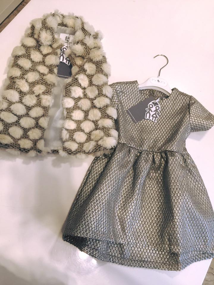 un abito e una pelliccia da bambina di color grigio