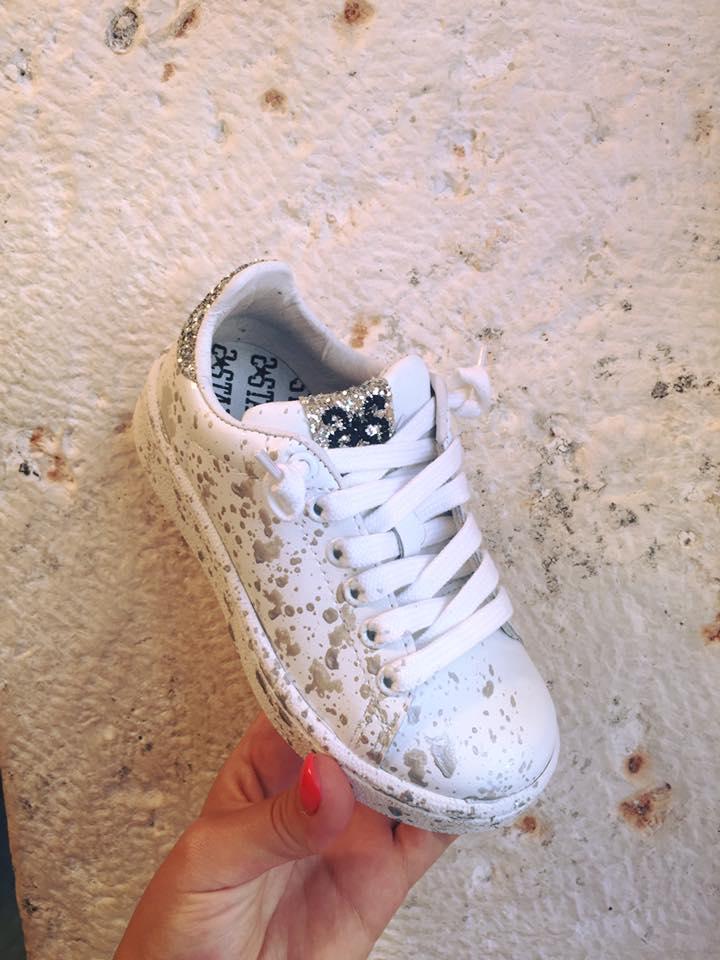 una scarpa da tennis di color bianco con disegni a schizzi di color beige