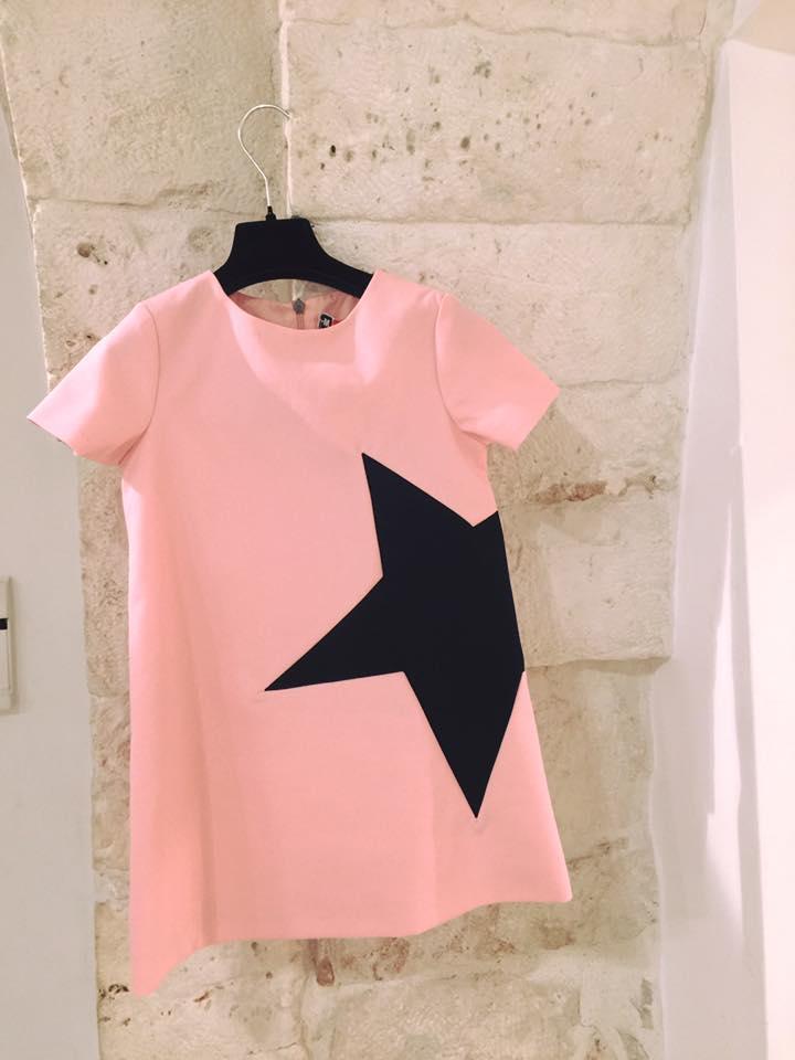 un abito da bambina di color rosa un disegno di una stella