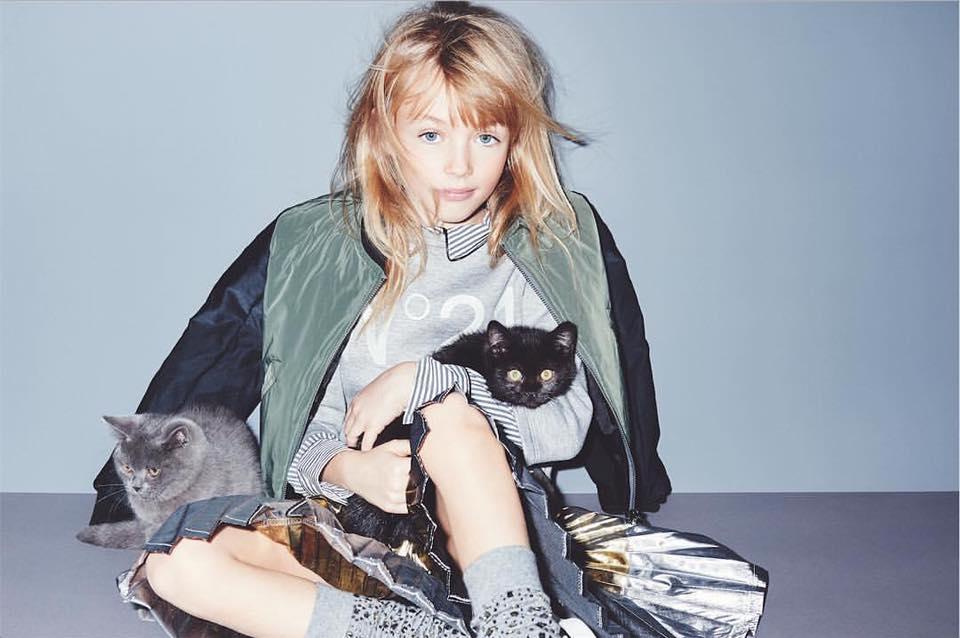 una bambina con un gold grigia e una felpa in posa con due gatti