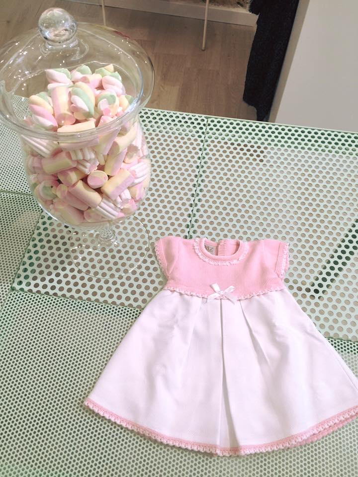 un abitino da bambina di color rosa con un fiocco