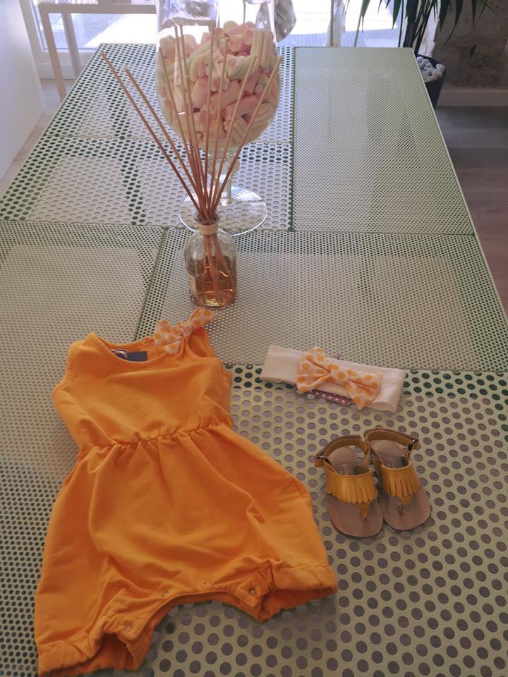 un vestito arancione con fiocco a pois e accanto dei sandali da bambina