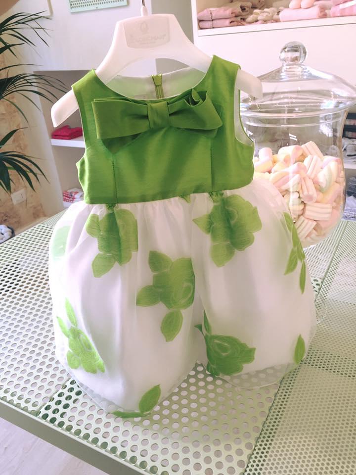 un appendino con un vestito da bambina di color bianco e verde