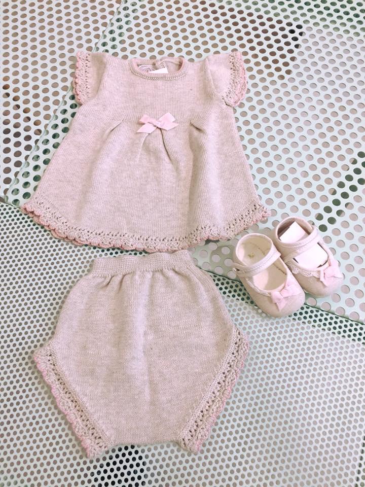 una maglietta, dei pantaloni e delle scarpine di color grigio da bambina