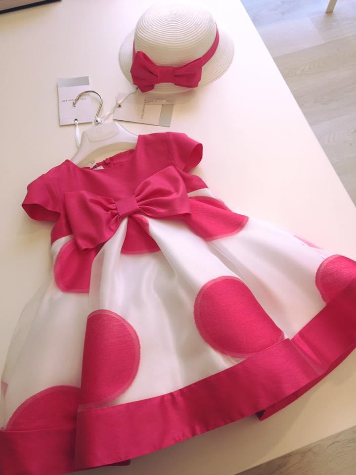 un abito da bambina di color bianco e fucsia con disegni a pois e un cappellino di paglia