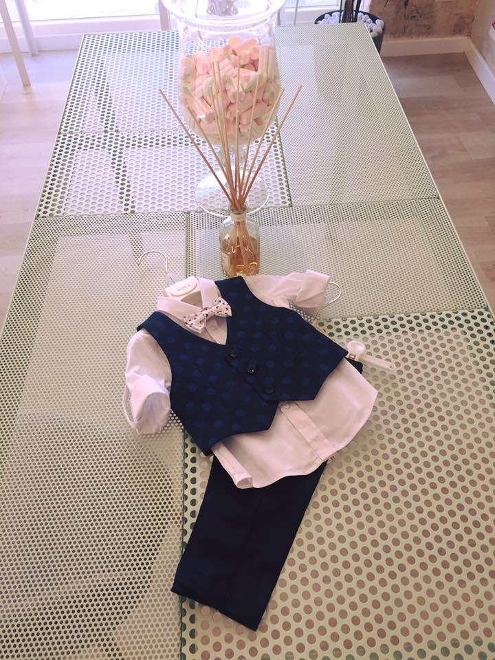 un completo con camicia bianca, pantaloni, gilet e papillon