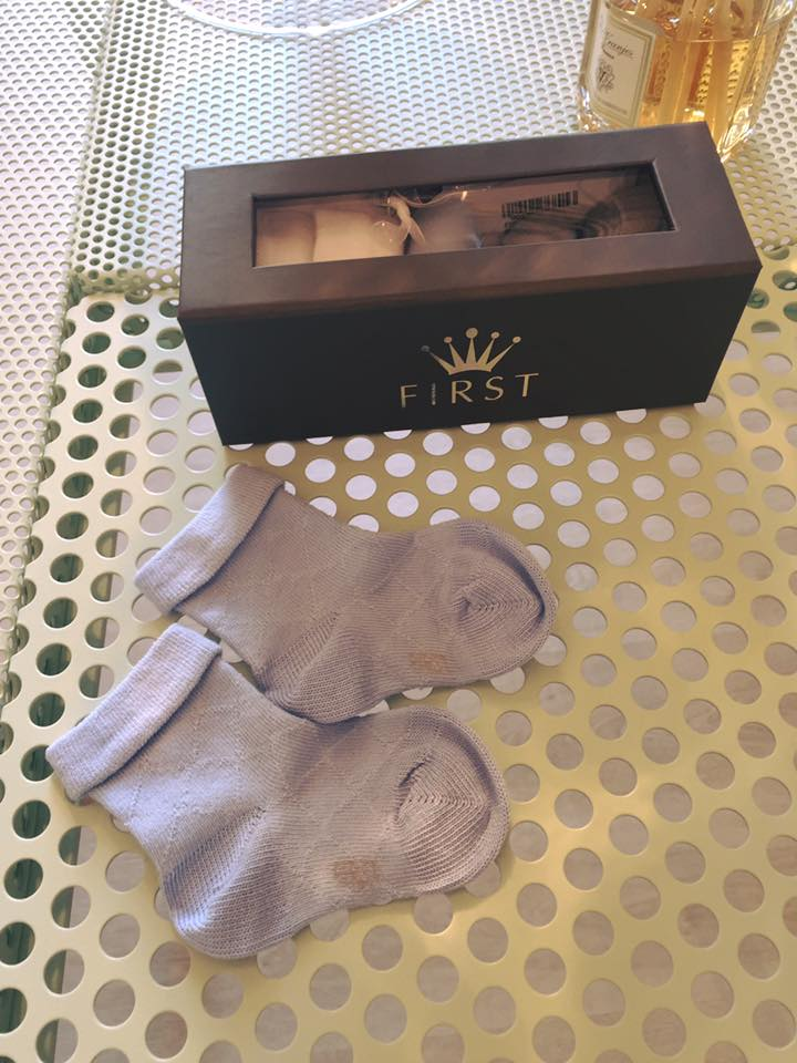 un paio di calzine di color azzurro e accanto una scatola di calze della marca First