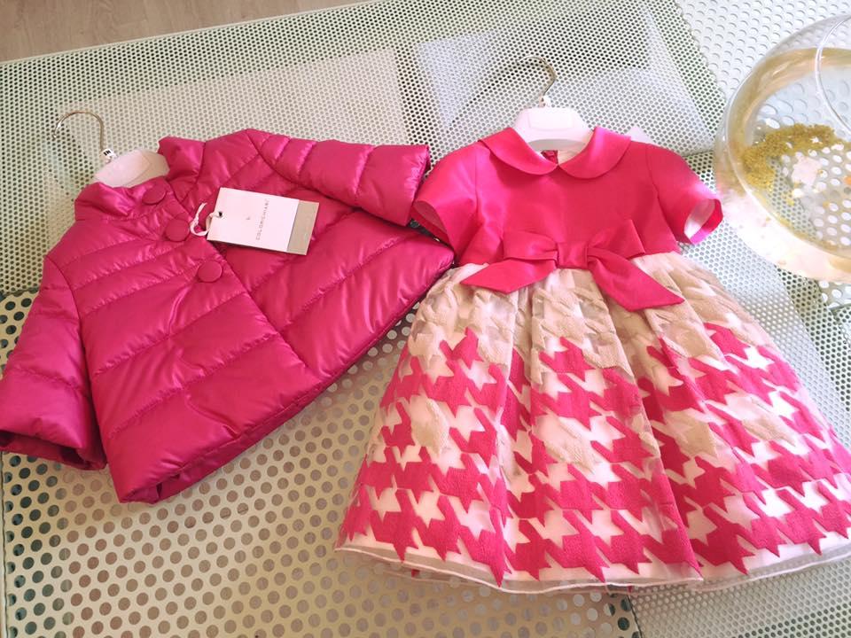 una giacca vento e un abito bianco e rosa da bambina