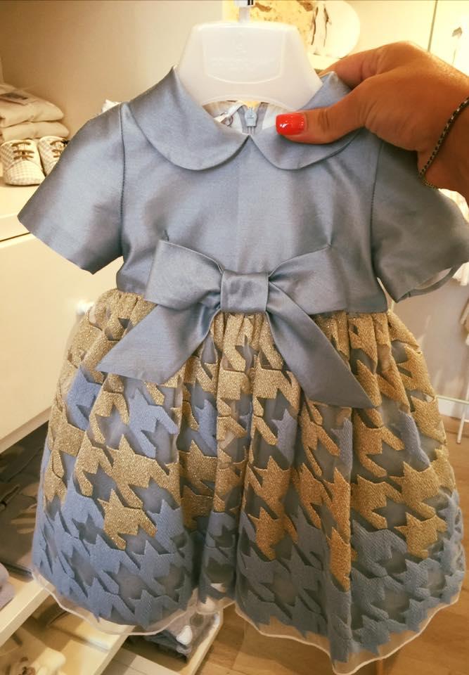 un abitino da bambina di color grigio e beige con un fiocco