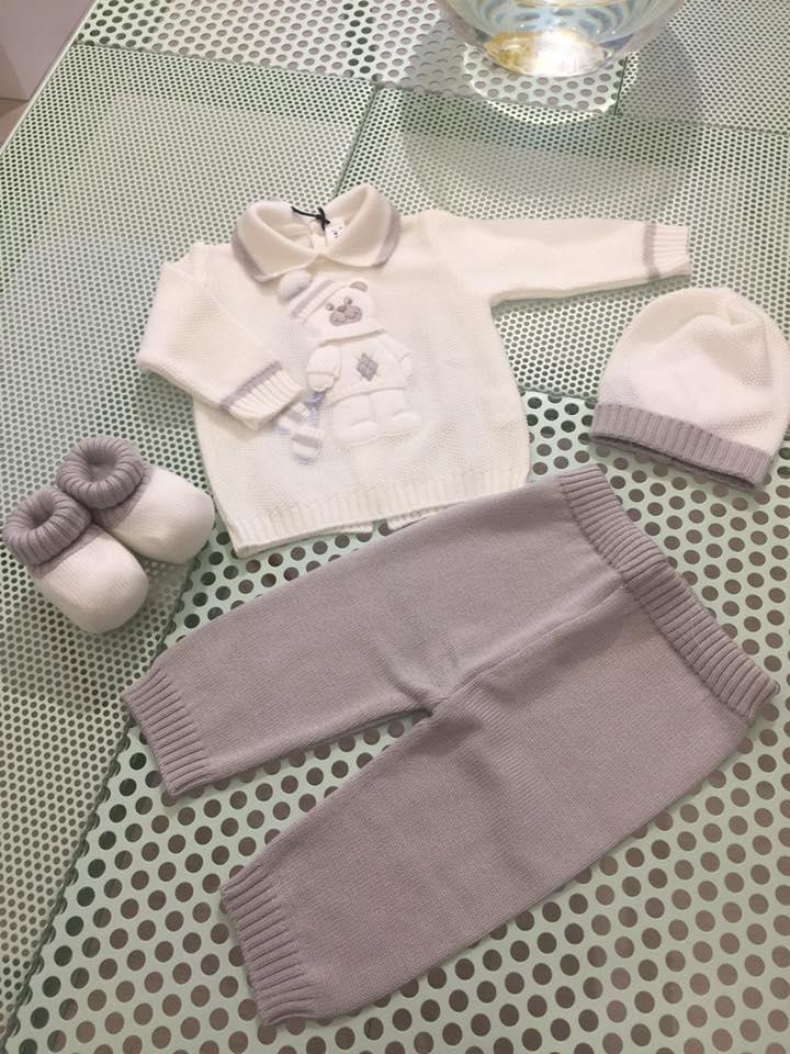 un completo da bambino con cappellino, pantaloni, maglia e pantofole di color bianco e grigio