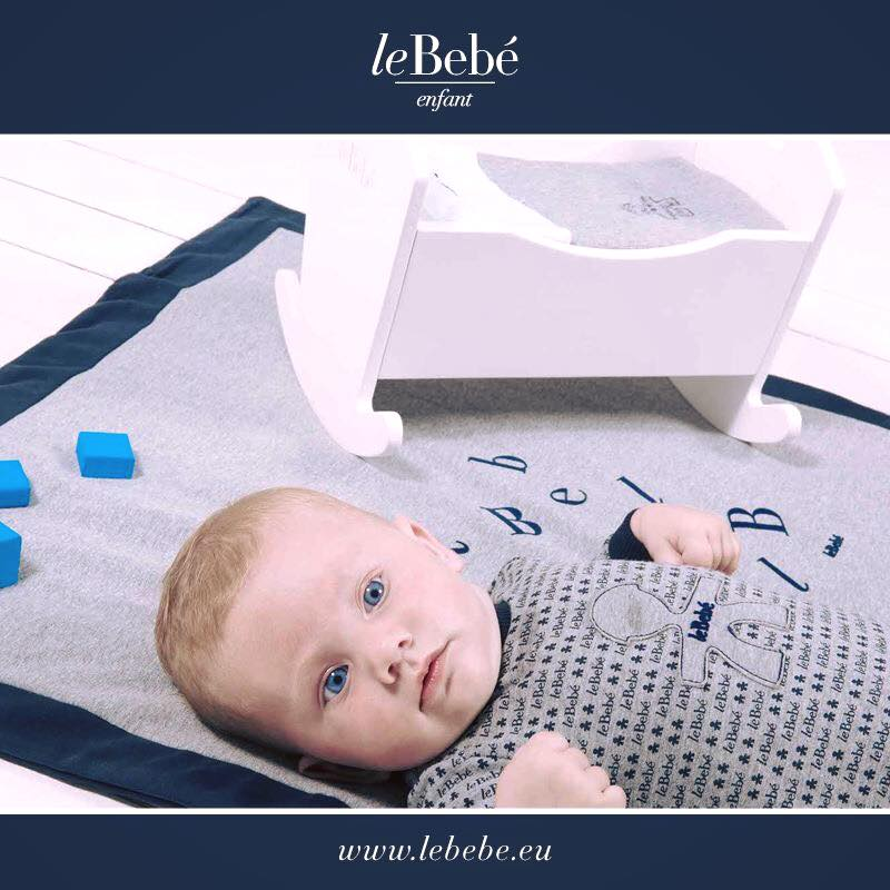 un neonato con una maglietta sdraiato sopra un asciugamano grigio