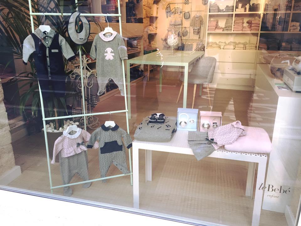 una vetrina con delle tutine grigie e abiti da neonati della marca Le Bebe'