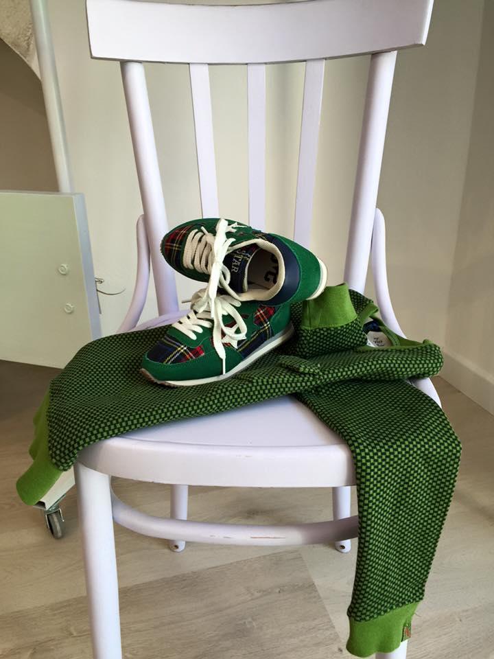 una sedia in legno di color bianco e sopra un paio di scarpe da bambino di color verde