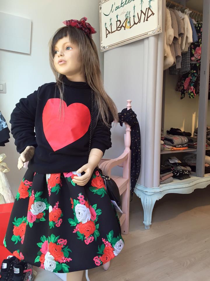 un manichino bambina con una maglia di color nero e una gonna di color nero e rosso