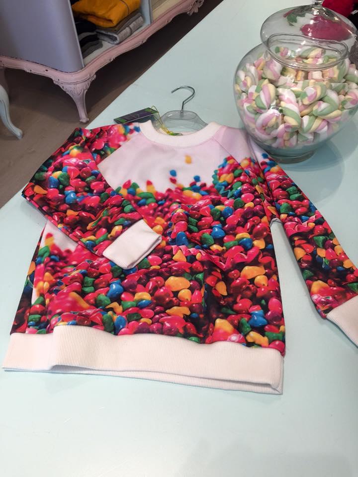 una maglia da bambini con sopra i disegni degli smarties