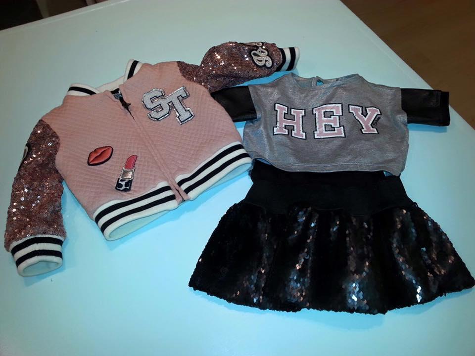 una felpa da bambini di color rosa e un abito di color nero e grigio